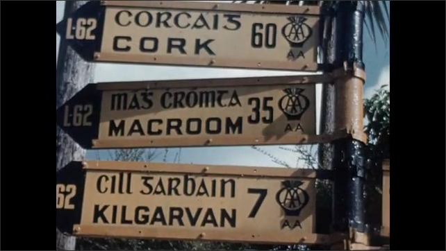 1950s: Street signs point in various directions. Text placard.