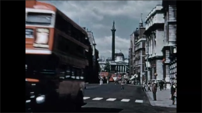 1950s: Water sprays from fountains in city. Text placard. Buses and crowds move through streets of Whitehall. Big Ben clock tower in London. Cars and buses drive past Big Ben.