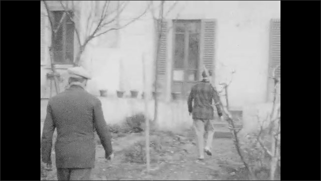 1940s: Men outside house, man passes in front of camera, man picks up cat. View of garden. Men in yard. Cat in garden. Men in front of house.