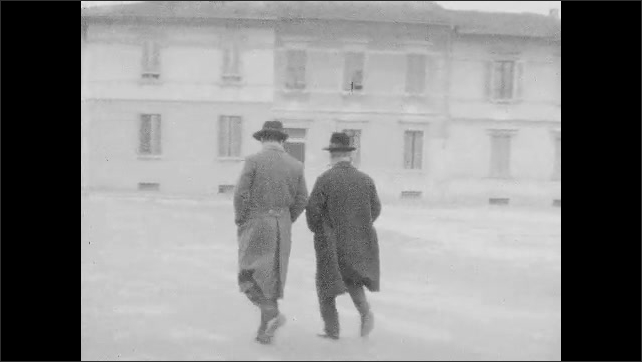 1940s: Family in front of house. Pan across carts in street. Men walk down street. Woman walks next to cart. Men and woman walking, pass by camera.
