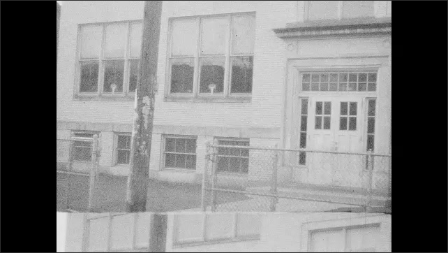 1940s: Pan across building. View of boat, pan across water.