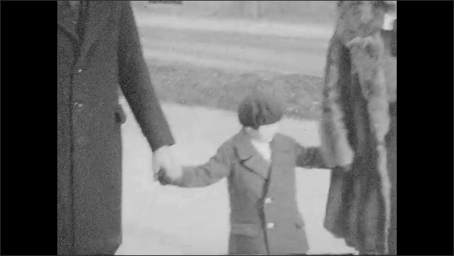 1940s: Man and woman walk down street with boy. Woman shakes man's hand, kisses boy. Views of man and woman standing with boy. Tilt up statue. Boy in front of statue.