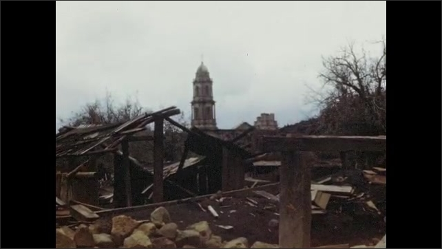1950s: Smoke rises from volcano, charred earth, destroyed village, lumber, rubble, bell tower, scrubby leafless trees.