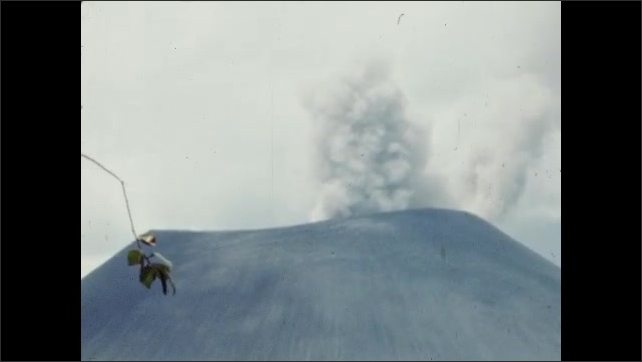 1950s: Smoke rises from volcano, lone pine tree, tree branch bobs. Destroyed village, rubble, lumber, leafless trees.