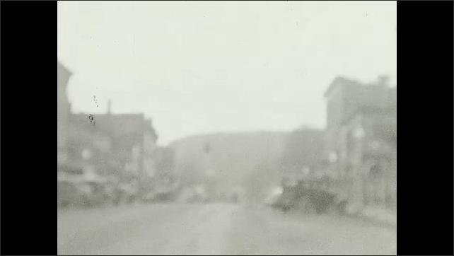 1940s: Car drives through town.  Train.