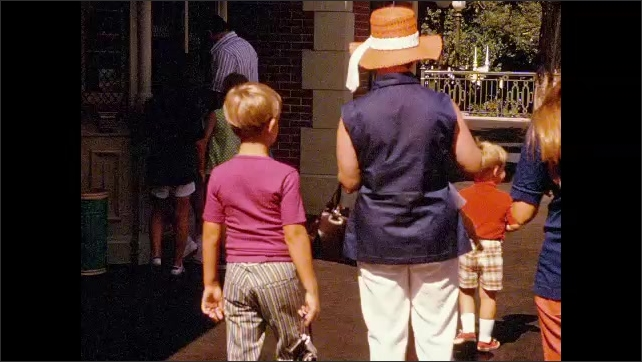 1970s: Family arrives at Disneyland. Mother and two young boys approach Santa Fe railway. Trolley goes by on Disney streetscape.