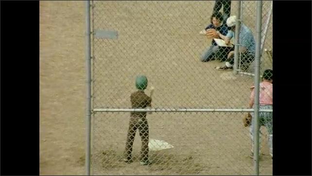 1970s: Overhead view of dirt baseball field. Children play on baseball field. Boy swings up at bat and strikes out. Boy runs to center field wearing baseball glove.