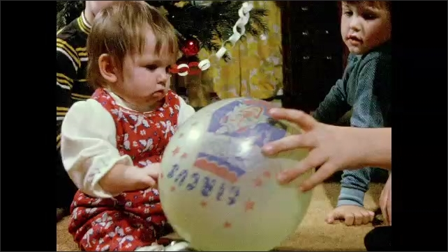 1970s: Brothers sit around baby girl in front of decorated Christmas tree. Brothers bring toys to her to amuse her. Baby girl plays with Circus printed balloon and puts it in her mouth.
