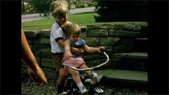 1970s: Toddler girl is lifted on to tricycle by older brother. Toddler girl walks next to tricycle and bends down and touches the mud.