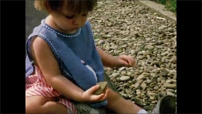 1970s: Toddler girl plays in gravel and grass. Older brother holds toddler girl by the hand and walks her down the driveway. Toddler girl walks unsteadily.