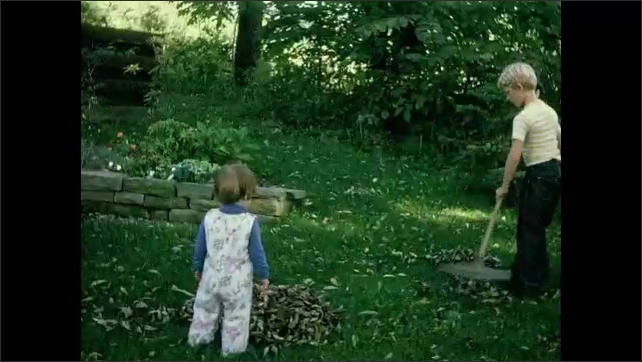 1970s: Brother rakes leaves in backyard as toddler sister watches.