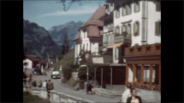 1940s: People walking down street of Swiss village as horse and buggy go by. Hillside leading up to mountain peak.