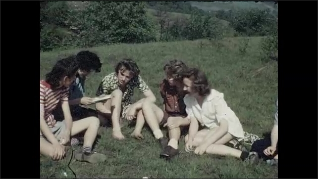 1940s: UNITED STATES: girls relax in sunshine in field. Girls sit in field. Girls and boys relax in outdoors.