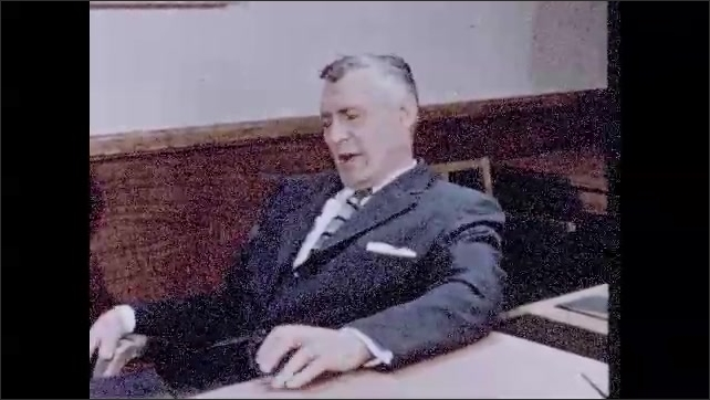 1950s: Man sits behind desk, leans back in chair, talks.