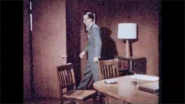 1950s: Two men sit at table, man put cigarette in ashtray, men stand up and walk out of room. Man sits in chair, shakes head.
