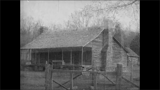 1930s: UNITED STATES: Double log cabin in frontier America. Two chimneys and long porch on house. Log farmhouse in mountains of Georgia