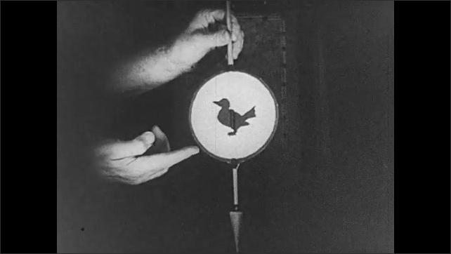 1930s: Hands spinning mutoscope to show images of bird and birdcage.