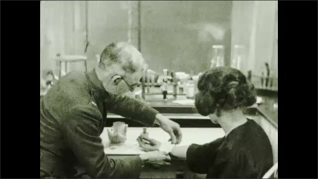 1930s: Man applies iodine to forearm of woman at table. Man applies gauze and bandage to woman's arm. Text placard.