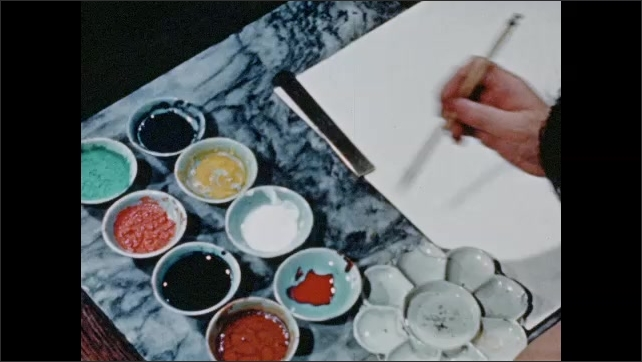 1940s: rows of bowls with watercolors sit on side of marble tabletop as hand uses paintbrush to mix colors in palette bowl with multiple saucers near art paper clamped to edge of desk.