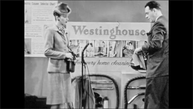 1940s: Salesman plugs in vacuum cleaner. Salesman speaks to woman. Salesman pours sand on carpet.