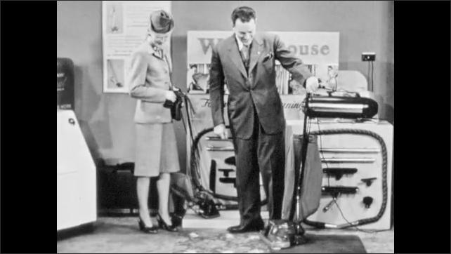 1940s: Salesman demonstrates vacuum cleaner. Salesman speaks to woman. Salesman and woman talk over vacuum demonstration.