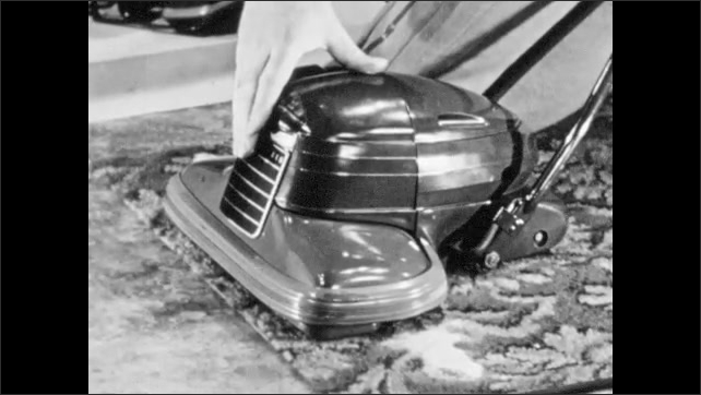 1940s: Vacuum cleaner tilts holding up carpet with suction. Hand touches vacuum and points to various parts.