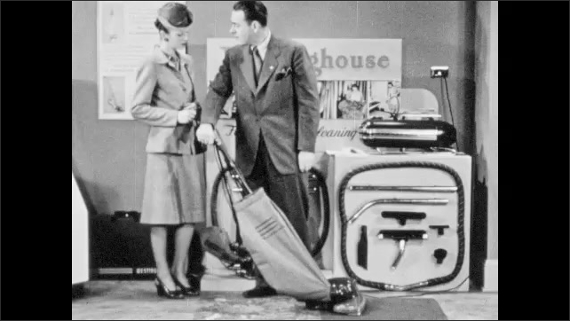 1940s: Woman pushes vacuum over carpet. Salesman interrupts and speaks to her. Woman tries vacuum cleaner once again. Woman and salesman talk.