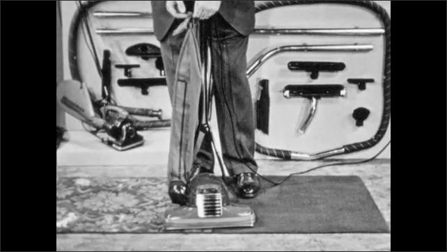 1940s: Salesman lifts and turns vacuum. Salesman demonstrates vacuum bag removal. Salesman points to headlight on vacuum.
