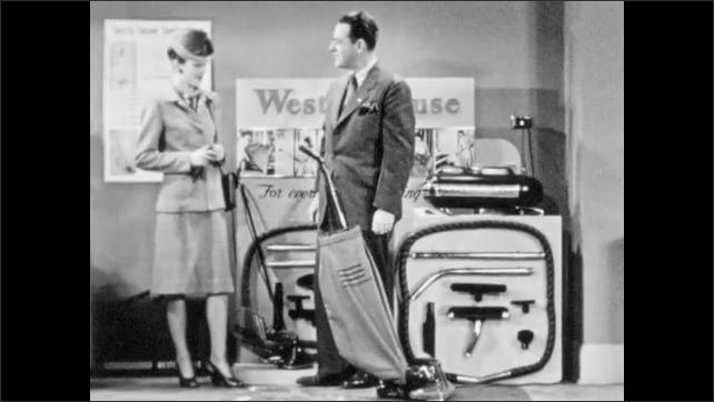 1940s: Salesman demonstrates vacuum cleaner handle positions. Salesman and woman talk. Salesman moves vacuum on carpet. Woman and man speak.