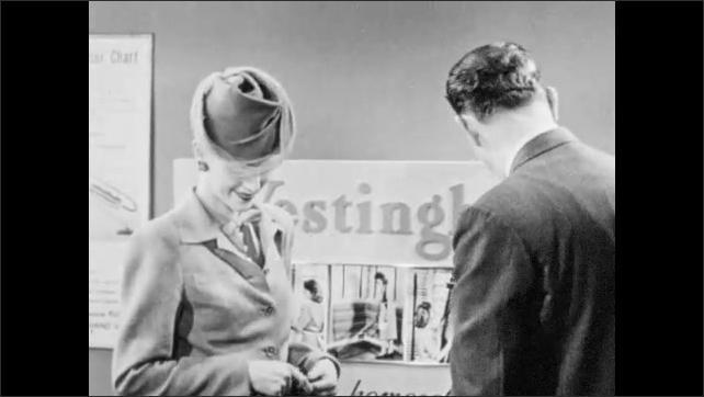 1940s: Salesman sits vacuum down and speaks to customer. Salesman retrieves rotating brush from display and speaks to woman.