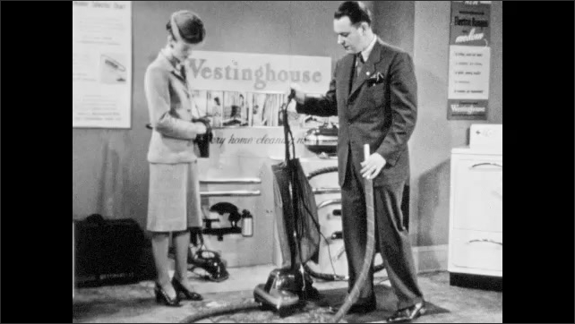 1940s: Home appliance showroom, salesman shows vacuum to woman, gestures, holds hose, demonstrates attaching part, nods, looks confident. Woman listens, talks.
