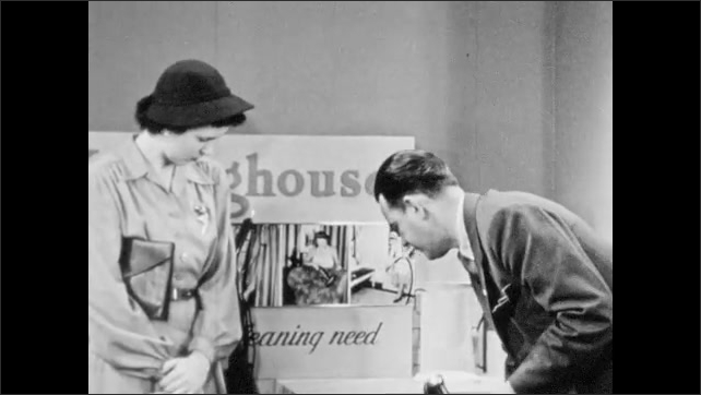 1940s: Home appliance showroom, salesman holds vacuum floor attachment, points, gestures, explains to woman, sets vacuum down, attaches floor brush, counts on fingers, nods emphatically.