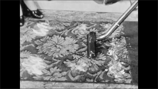 1940s: Home appliance showroom, salesman demonstrates vacuum, scrubs dirty carpet with floor attachment back and forth. Woman watches. Man runs upright vacuum across carpet slowly.