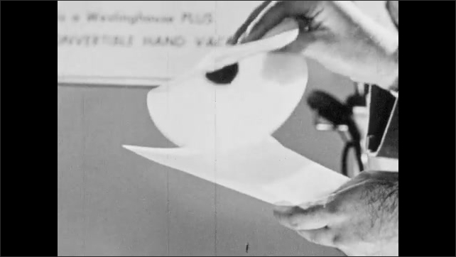 1940s: Home appliance showroom, salesman uses tweezers to manipulate fibers and dirt on filter paper, empties out dirt onto other paper, folds corner, rubs paper.