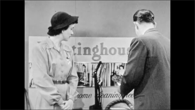 1940s: Home appliance showroom, vacuum salesman talks to woman, holds paper, woman talks, listens. Man picks up dirty filter paper, shows it to woman. Woman looks, nods.