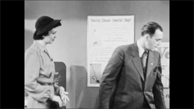 1940s: Westinghouse salesman shows woman storage bag for vacuum cleaner. Man points at woman, talks. Man holds vacuum cleaner hose nozzle and gestures to Westinghouse poster.
