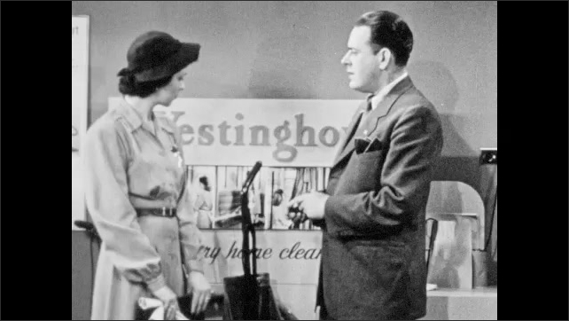 1940s: Man holds vacuum cleaner attachments in front of photographs of women using vacuum cleaners. Salesman talks to woman, holding vacuum attachments. Man lifts vacuum on to display pedestal.