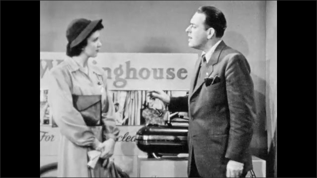 1940s: Salesman and woman stand in Westinghouse vacuum cleaner showroom, salesman gestures to and touches vacuum cleaner as he talks. Man takes out bill of sale.
