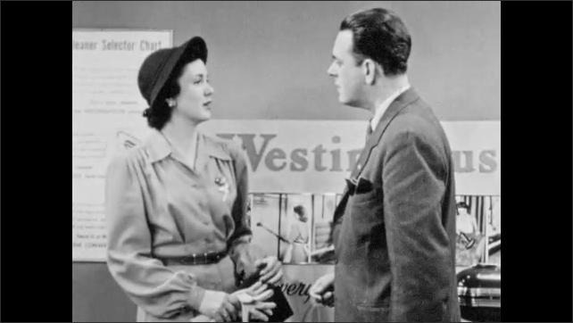 1940s: Salesman and woman stand in Westinghouse vacuum cleaner showroom talking, man writes on notepad and woman smiles. Man and woman talk. Man demonstrates vacuum cleaner.