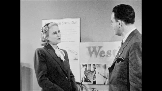 1940s: Salesman stands in Westinghouse vacuum showroom, points at empty space, woman appears. Man talks, woman talks. Man holds chin thoughtfully, then responds to woman.