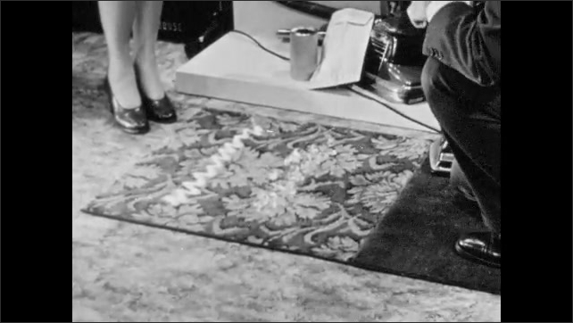 1940s: Westinghouse salesman makes carpet messy for vacuum demonstration. Salesman demonstrates vacuum, sweeping line through dirt on carpet.