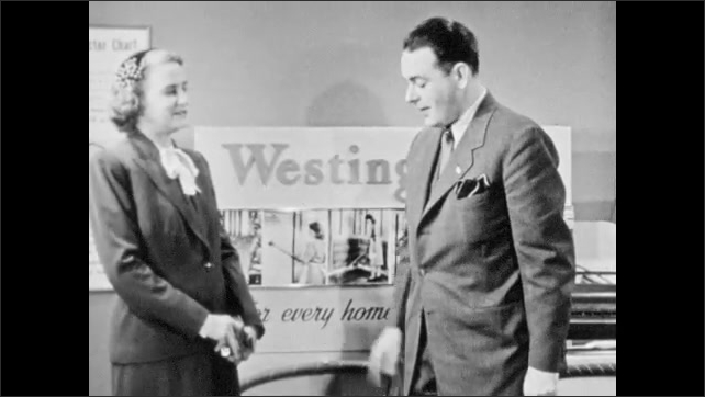 1940s: Westinghouse salesman talks to customer. Westinghouse salesman demonstrates product and shows customer filter paper for vacuum.
