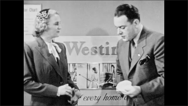 1940s: Westinghouse vacuum salesman puts greasy filter paper on arm of suit and points at grease ring. Salesman talks to woman customer.