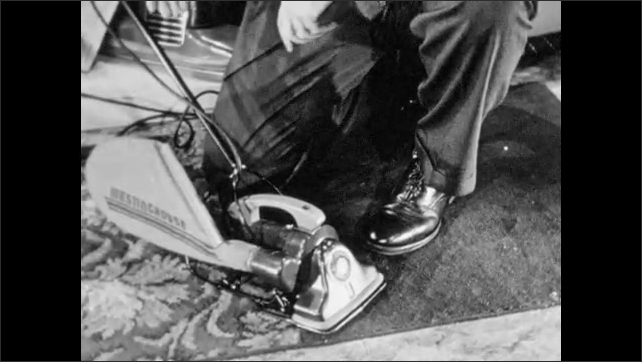 1940s: Westinghouse salesman squats on floor and demonstrates how convertible vacuum cleaner goes from floor cleaner to hand cleaner. Salesman holds hand cleaner and shows customer.