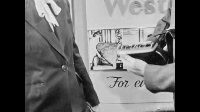 1940s: Westinghouse vacuum salesman demonstrates hand vacuum brush to customer. Salesman taps vacuum cleaner, removes bag, and puts filter paper between vacuum and bag.
