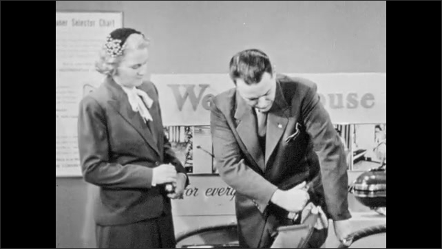 1940s: Westinghouse vacuum salesman uses hand vacuum on his own suit sleeve in front of woman customer. Salesman turns off vacuum and hands woman filter paper. Woman talks.