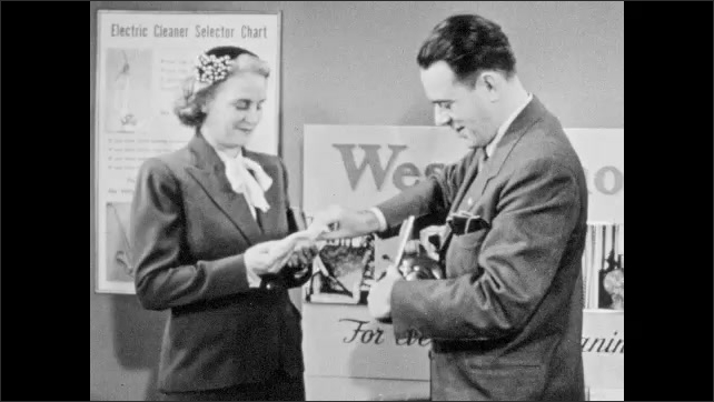 1940s: Salesman holds vacuum filter paper, showing dirt. Woman customer and salesman talk and smile. Salesman passes handvac to woman. Salesman shows woman vacuum switches.