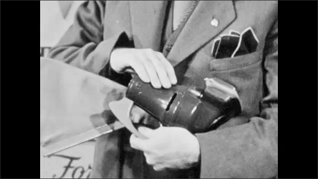 1940s: Westinghouse salesman holds hand vacuum cleaner, touches nozzle, flips cleaner over. Salesman holds cleaner and speaks to woman customer.