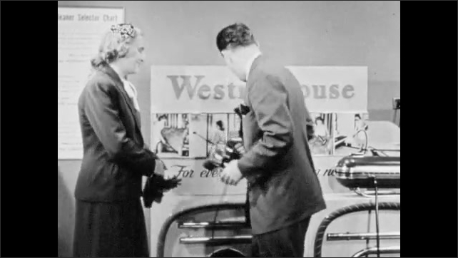 1940s: Westinghouse salesman and woman customer talk, as salesman demonstrates hand vacuum cleaner. Woman puts on gloves and salesman gets out pad and pen and begins writing, while grinning.