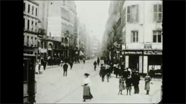 """1930s: Busy cityscape with trams and people. Intertitle """"The raw silk is spun by a month-caterpillar. The female moth lives but 3 days, during which time she lays 500 eggs""""."""